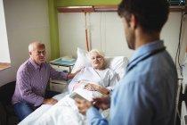 Paziente anziano che interagisce con il medico in ospedale — Foto stock