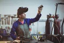 Чоловічий зварювальник вивчення шматок металу в майстерні — стокове фото