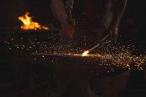 Forgeron travaillant sur une tige de fer chauffée en atelier — Photo de stock