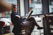 Деловая женщина, читающая газету в кафе — стоковое фото