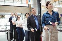 Пассажиры, стоящие в очереди у стойки регистрации с багажом внутри терминала аэропорта — стоковое фото