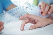 Image recadrée d'un physiothérapeute examinant le doigt d'une patiente avec goniomètre en clinique — Photo de stock