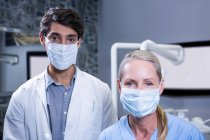 Portrait of dentist and dental assistant in surgical masks at dental clinic — Stock Photo