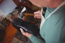 Sapateiro martelando em um sapato na oficina — Fotografia de Stock