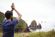 Vista posteriore dell'uomo che esegue yoga sulla scogliera — Foto stock