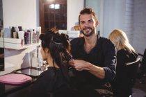 Portrait de coiffeur souriant travaillant sur le client au salon de coiffure — Photo de stock