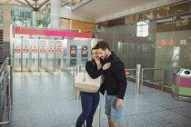 Casal abraçando uns aos outros no aeroporto — Fotografia de Stock