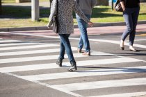 Low section of people crossing the road in daylight — Stock Photo