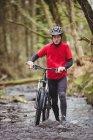 Portrait de cycliste marchant à vélo dans le ruisseau à la forêt — Photo de stock