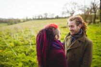 Усміхаючись пара холдингу руки, поки стоїть на травою поле в парку — стокове фото