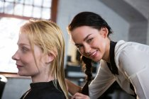 Hairstylist combing client hair in salon — Stock Photo