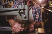 Средняя часть сапожника с помощью швейной машинки в мастерской — стоковое фото