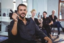 Portrait of smiling hairdressers sitting on chairs in salon — Stock Photo