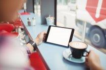 Image recadrée d'une personne tenant une tablette avec du café au restaurant — Photo de stock