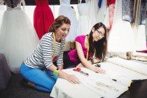 Женщины-модельеры, работающие над ноутбуком в студии — стоковое фото