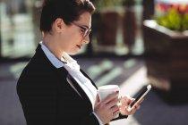 Vista laterale della giovane donna d'affari che utilizza il telefono cellulare — Foto stock