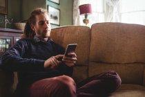 Молодой хипстер использует мобильный телефон на диване дома — стоковое фото