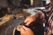 Cropped image of goldsmith shaping metal with pliers in workshop — Stock Photo