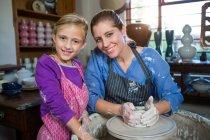 Портрет усміхнене жіночий Поттер допомога дівчині в гончарної майстерні — стокове фото