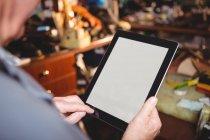 Sapateiro usando tablet digital na oficina — Fotografia de Stock