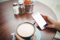 Cropped image of person holding phone while having coffee at restaurant — Stock Photo