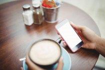 Кадроване зображення особою, телефон маючи кави в ресторані — стокове фото