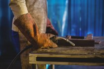 Cropped image of male welder holding welding torch in workshop — Stock Photo