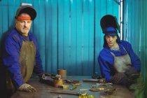 Портрет чоловічих і жіночих зварювальник стояли разом у майстерні — стокове фото