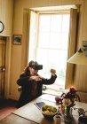 Hipster disfrutando mientras usa el simulador de realidad virtual en casa - foto de stock