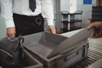 Mann steckt Laptop in Tablett für Sicherheitskontrolle am Flughafen — Stockfoto