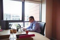 Homem de negócios trabalhando no laptop no escritório — Fotografia de Stock