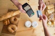 Immagine ritagliata di donna che effettua il pagamento con carta di credito in caffetteria — Foto stock