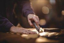 Руки сапожника режут кусок кожи в мастерской — стоковое фото