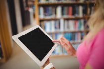 Cropped image of Woman using digital tablet in library — Stock Photo