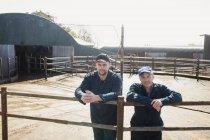 Portrait de collègues debout près de la clôture à la grange — Photo de stock