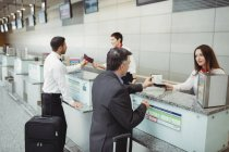 Flugbegleiter reichen Passagieren am Flughafen-Check-in-Schalter den Reisepass — Stockfoto