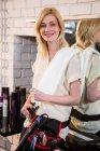Портрет усміхнене жіночий перукар холдингу ножиці в салон — стокове фото