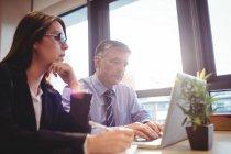 Empresario discutiendo con colega sobre portátil en la oficina - foto de stock