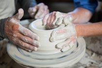 Imagem cortada do oleiro masculino ajudando oleiro feminino na oficina de cerâmica — Fotografia de Stock