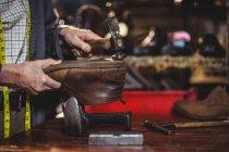Hands of shoemaker hammering on a shoe in workshop — Stock Photo