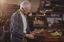 Чоботар ремонту взуття в майстерні — стокове фото