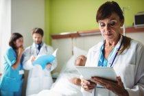 Женщина-врач с помощью цифрового планшета в больнице — стоковое фото
