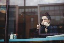 Pensativa jovem beber café no café visto através de vidro — Fotografia de Stock