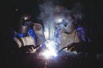 Два зварювальні роботи на шматок металу в майстерні — стокове фото
