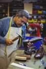 Mixed race senior shoemaker hammering on a shoe in workshop — Stock Photo