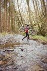 Вид сбоку на велосипедиста, перевозящего велосипед при пересечении ручья в лесу — стоковое фото