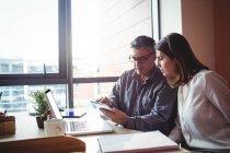 Homme et femme discutant sur tablette numérique au bureau — Photo de stock