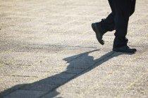 Baixa seção de homem andando na rua à luz do dia — Fotografia de Stock