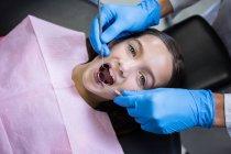 Вивчаючи молоді пацієнта з інструментами на Стоматологічна клініка стоматолог — стокове фото