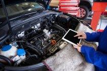 Imagem cortada de Mecânico usando tablet digital durante a manutenção do motor do carro na garagem de reparação — Fotografia de Stock